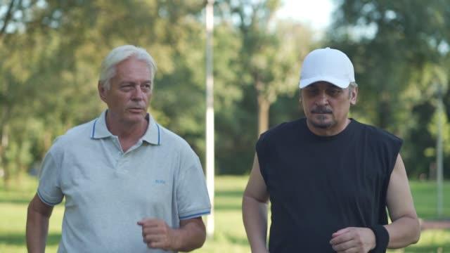 vídeos de stock, filmes e b-roll de homens seniores ativos correndo juntos em um parque - amizade masculina
