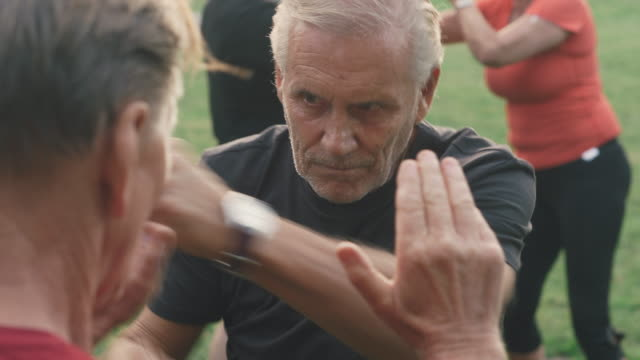 active senior men working out by boxing in park - martial arts stock videos & royalty-free footage