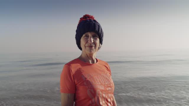 active senior posing in front of a cold sea before swimming - cold temperature stock videos & royalty-free footage
