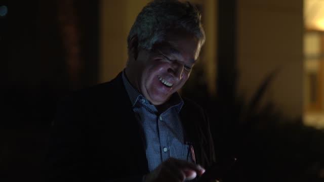 vídeos de stock, filmes e b-roll de veterano ativo usando seu celular à noite - só um homem