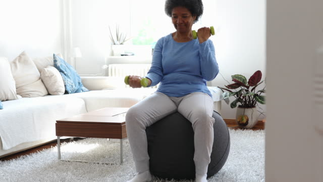 active senior woman exercising at home during covid-19 pandemic - healthy lifestyle stock videos & royalty-free footage