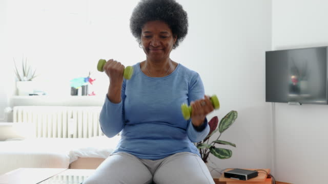 active senior woman exercising with dumbbell at home - hand weight stock videos & royalty-free footage