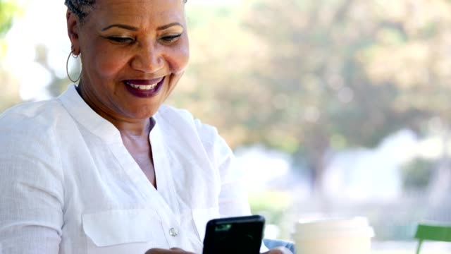 active senior woman laughs while texting with her family - pavement cafe stock videos & royalty-free footage