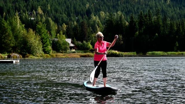 active senior woman paddle boarding on vacation - eyewear stock videos & royalty-free footage
