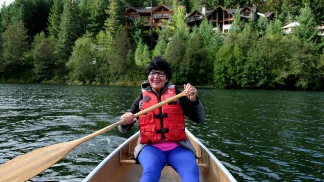 vídeos y material grabado en eventos de stock de mujer mayor activa remando - kayak barco de remos