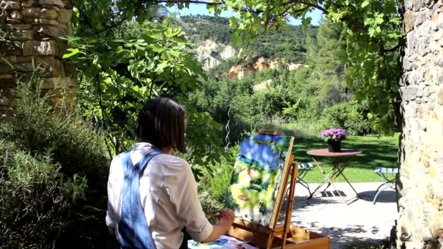 Active senior woman painting outdoors at an easel, video