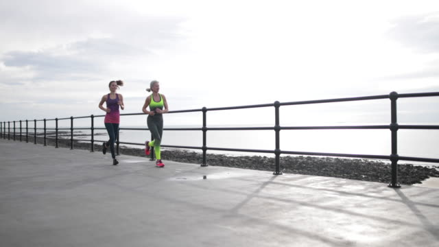active senior woman running with younger woman - man made stock videos & royalty-free footage