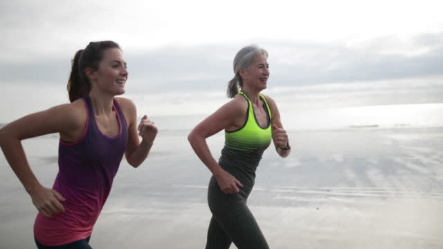 Active senior woman running with younger woman