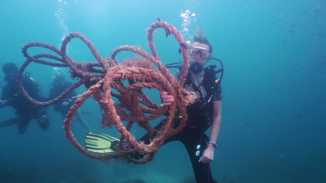 active senior woman scuba diver cleaning underwater ghost net pollution - aqualung diving equipment stock videos & royalty-free footage