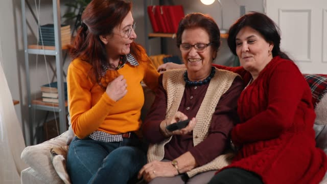 active senior women and her two daughter watching television - three people stock videos & royalty-free footage
