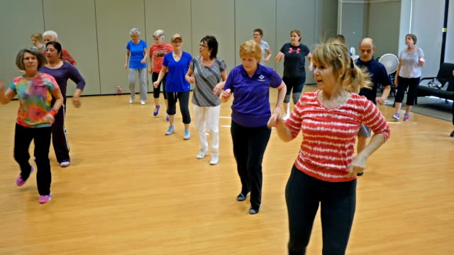 Active seniors enjoy dancing in exercise class