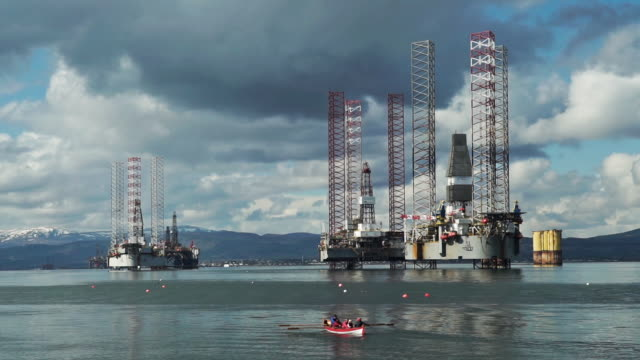 active seniors in rowing boat approaching oil drilling platform - gas stock videos & royalty-free footage