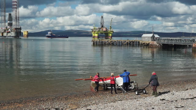 active seniors launching rowing boat near offshore oil platform rig - environmentalist stock videos & royalty-free footage