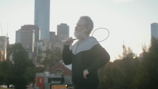 vídeos de stock, filmes e b-roll de idosos ativos jogando badminton (câmera lenta) - badmínton esporte