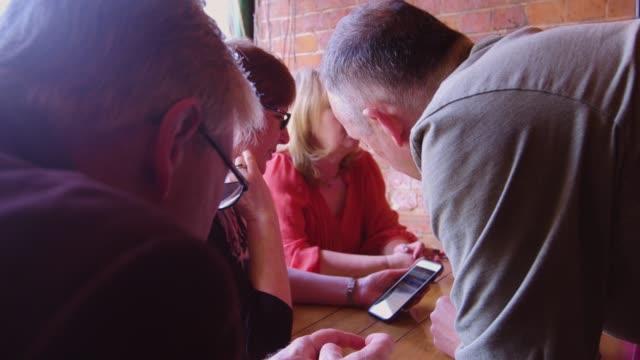 Active Seniors Sharing Something on Phone Screen