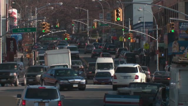 Active shot of traffic on east tremont avenue in the bronx near park avenue, washington avenue and a junction to I95 North during the day