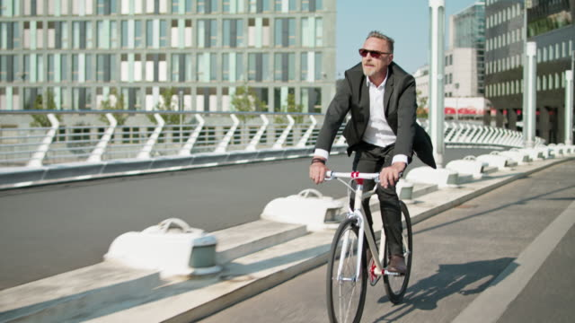 active, sporty and healthy business man in his early 60s with short greying hair and grey beard enjoys urban lifestyle in summer, he wears a black garment while riding his trendy single speed city bike. - nachhaltigkeit stock-videos und b-roll-filmmaterial