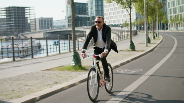 active, sporty and healthy business man in his early 60s with short greying hair and grey beard enjoys urban lifestyle in summer, he wears a black garment while riding his trendy single speed city bike. - sonnenbrille stock-videos und b-roll-filmmaterial