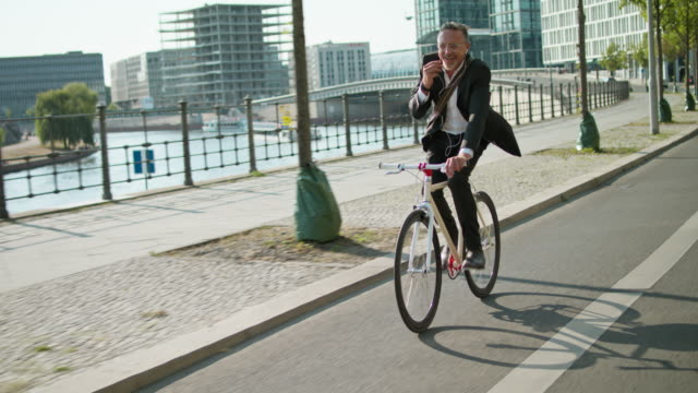 active, sporty and healthy business man in his early 60s with short greying hair and grey beard enjoys urban lifestyle in summer, he wears a black garment while riding his trendy single speed city bike. - environmental conservation stock-videos und b-roll-filmmaterial