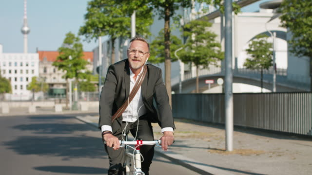 Active, sporty and healthy business man in his early 60s with short greying hair and grey beard enjoys urban lifestyle in summer, he wears a black garment while riding his trendy single speed city bike.