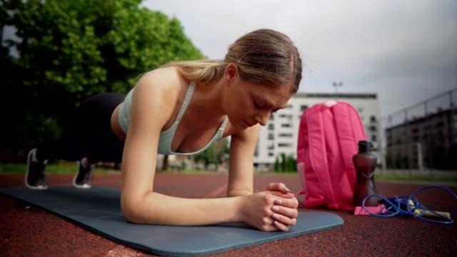 vídeos y material grabado en eventos de stock de mujer activa haciendo ejercicio al aire libre - entrenamiento sin material