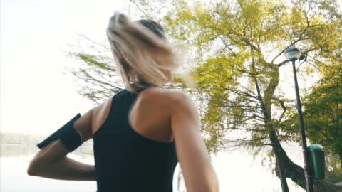 vídeos de stock e filmes b-roll de active woman running in the park. - young women