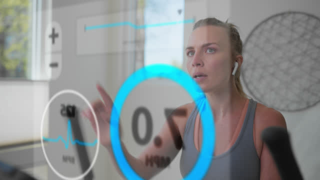 active woman uses a holographic display to adjust her workout settings - internet of things stock videos & royalty-free footage