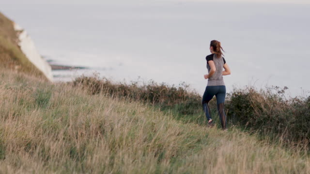 Active young adult female running on cliff by sea