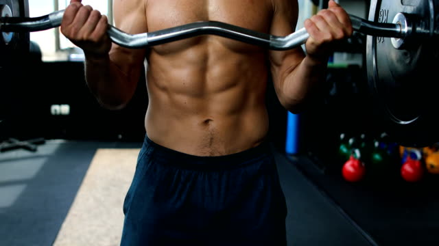 vídeos de stock e filmes b-roll de active young man having strength exercise with barbell in a gym - body building