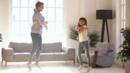 Active young mom and kid daughter dancing in living room