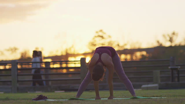 active young woman wearing protective face mask does yoga on a mat outdoors at sunset - barefoot stock videos & royalty-free footage
