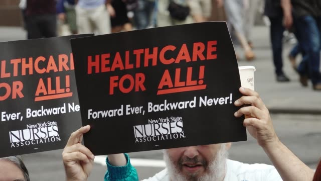 vídeos y material grabado en eventos de stock de activist and healthcare advocates held a rally at the 5th avenue trump tower titled 'our lives are still on the line celebration recommitment rally'... - medicare