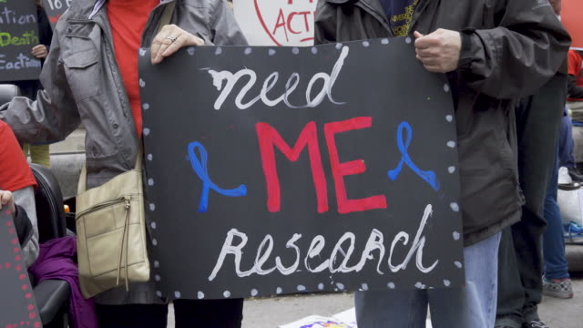 vídeos de stock, filmes e b-roll de activist and people suffering from 'me' rallied at columbus circle 59th street to call on governments and health officials to take action for people... - doença crônica