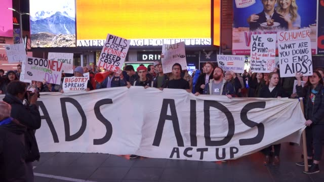 activist from the organization 'act up' activist rallied in duffy square times square in light of the upcoming annual world aids day. the rally... - レトロウィルス点の映像素材/bロール