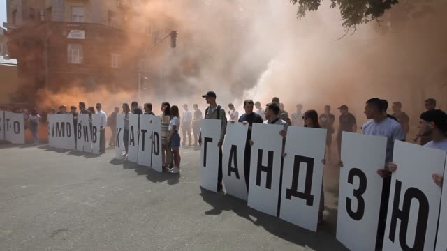 Activists burn flares and hold words ' Who ordered Katya Handziuk' as they demand to investigate and punish the organizers and assassins of Kateryna...
