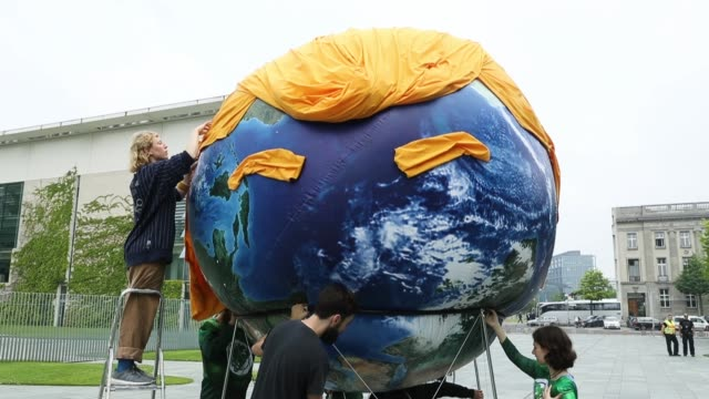 vídeos de stock, filmes e b-roll de activists decorate a balloon painted to look like planet earth with orange hair and eyebrows in the likeness of us president donald trump during a... - sátira