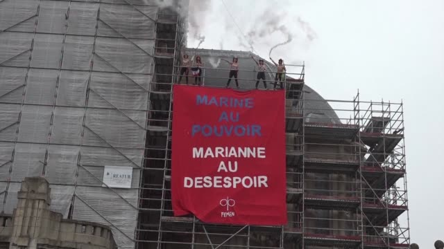 activists from the femen women's group drape an antifront national banner on a church in heninbeaumont a town in one of the farright party's... - national front stock videos and b-roll footage