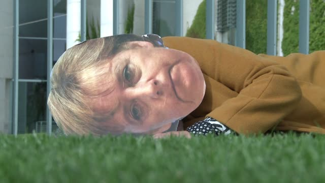 vídeos de stock e filmes b-roll de activists from the young socialists in the spd and the pirate party parody a fake angela merkel lying down in front of the chancellery to symbolise... - sátira