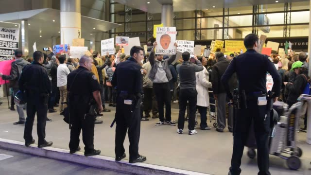 vídeos de stock, filmes e b-roll de activists gather at los angeles international airport to protest the travel ban from muslim-majority countries enacted by us president donald trump... - decretar