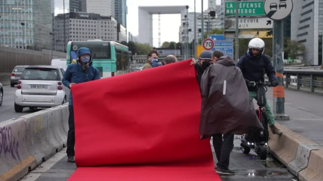 "activists install a red carpet on a cycle path as the collectif ""vélo île-de-france"" organises a happening on the ""coronapiste"" of pont de neuilly in... - île de france stock-videos und b-roll-filmmaterial"