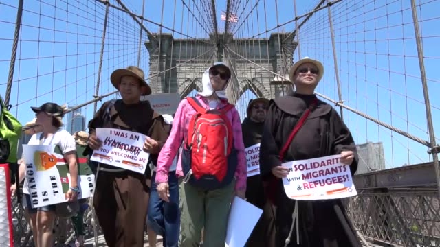activists march across the brooklyn bridge during a rally to protest the trump administration's immigration policy on june 30, 2018 in new york, usa. - brooklyn bridge stock videos & royalty-free footage