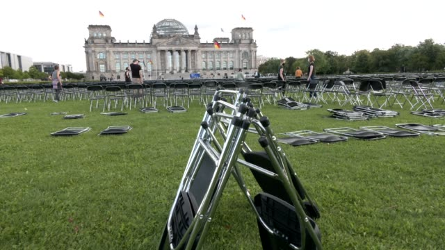 activists place 13,000 chairs in front of the reichstag building, seat of the german lower house of parliament bundestag in an action to call for the... - grecia stato video stock e b–roll