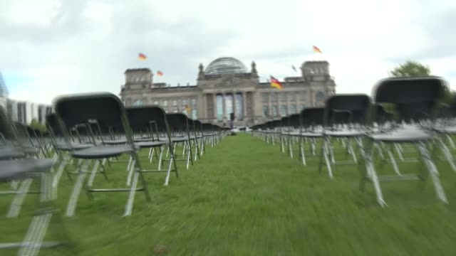 vídeos y material grabado en eventos de stock de activists place 13,000 chairs in front of the reichstag building, seat of the german lower house of parliament, in an action to call for the... - centro de berlín