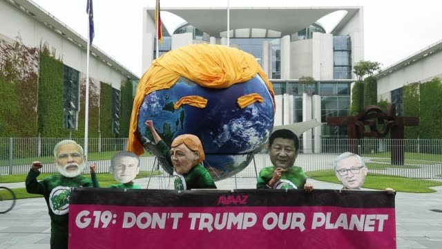 activists wearing masks with the faces of g20 state leaders in front of a balloon painted to look like planet earth and decorated with orange hair... - satire stock-videos und b-roll-filmmaterial