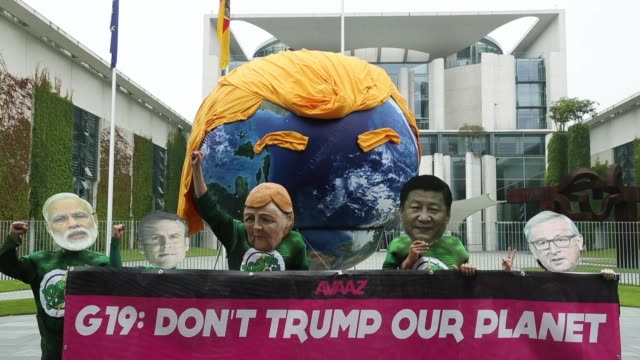 Activists wearing masks with the faces of G20 state leaders in front of a balloon painted to look like planet Earth and decorated with orange hair...