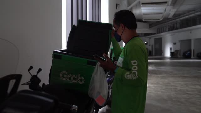 activities at grabfood, grab holdings inc.'s online food-delivery platform's kitchen in singapore city, singapore, on wednesday, april 28, 2021. - crash helmet stock videos & royalty-free footage