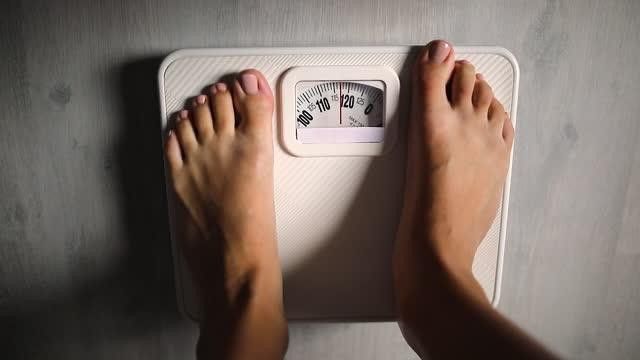 vídeos y material grabado en eventos de stock de actividad con la pierna del soporte de la mujer que mide la escala de peso para la dieta con los pies descalzos - medir