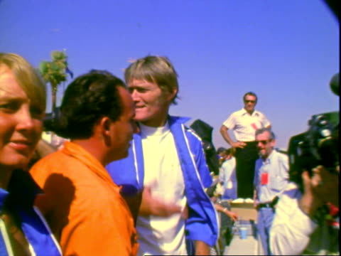 actor and motor sports enthusiast james garner wearing sunglasses dark blue racing jacket while talking joking with fellow actor chuck connors at... - army helmet stock videos & royalty-free footage