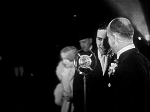 b/w 1928 actor charles 'buddy' rogers talking into microphone at interference premiere / newsreel - 1928年点の映像素材/bロール