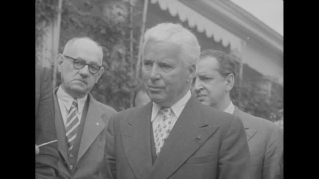 vídeos de stock, filmes e b-roll de actor charlie chaplin stands with group of people outside his manoir de ban estate in corsiersurvevey switzerland during a brief ceremony at which he... - 1952